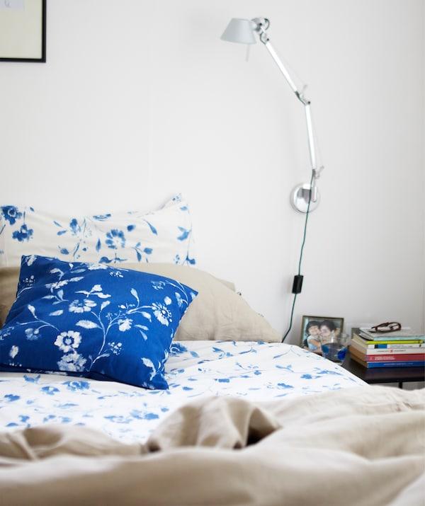 床上铺有带蓝色和白色花卉图案的床上用品,上方的白色墙壁上设有银色阅读灯。