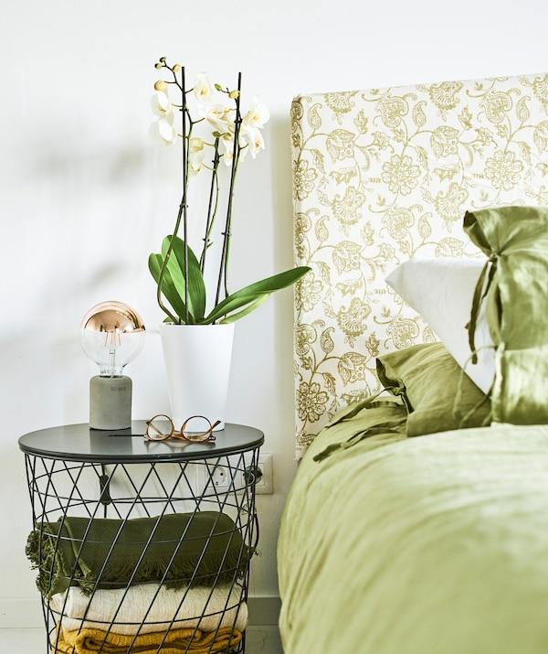 床上铺着绿色的床上用品,床头板包裹着绿色佩斯利涡旋图案布料,眼镜和一株兰花放置在金属丝床边桌上。
