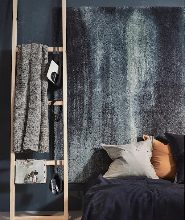 床尾旁摆放着类似梯子的搁架单元边框,边框板条上挂着书、休闲毯和耳机。