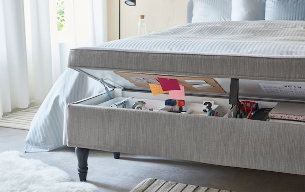 床尾设有包覆纺织品的储物长凳,盖子半开,里面存放着典型的家庭办公用品。