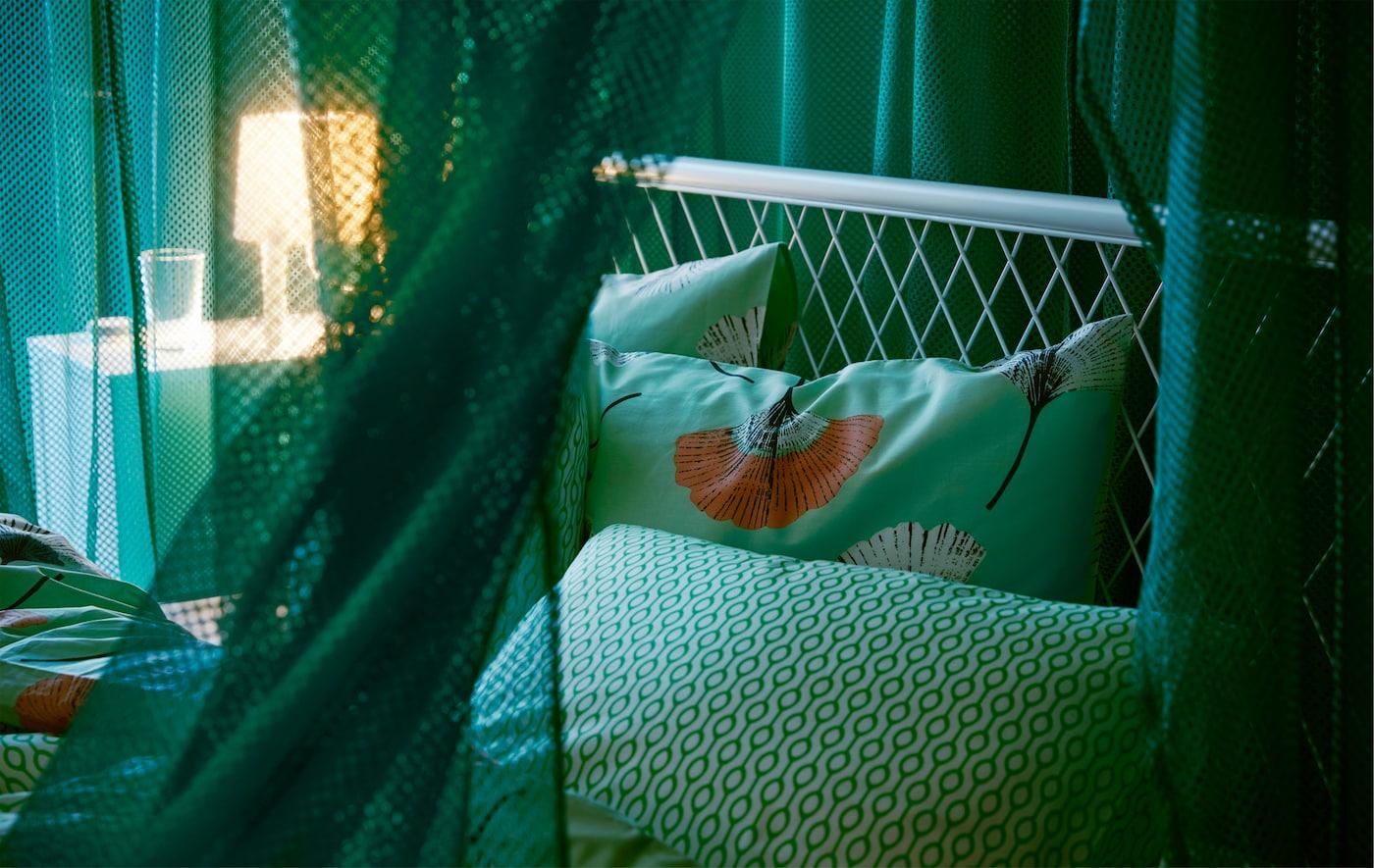"""垂挂着的宜家 GRÅTISTEL 格拉第德 绿色网帘在房间内打造出一个""""国中之国"""",同时还能透过少许光线。"""