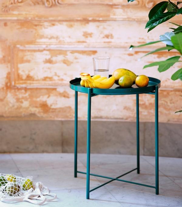 瓷砖地面上摆放着翡翠绿色的托盘桌。桌子上有香蕉和许多柑橘类水果。