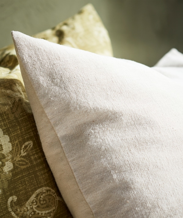 Close-up of a beige pillow in natural cotton material shown next to a green paisley patterned pillow.