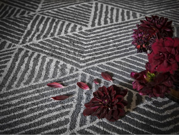 Close-up of a grey rug with a geometric pattern and some red flowers scattered on the rug.