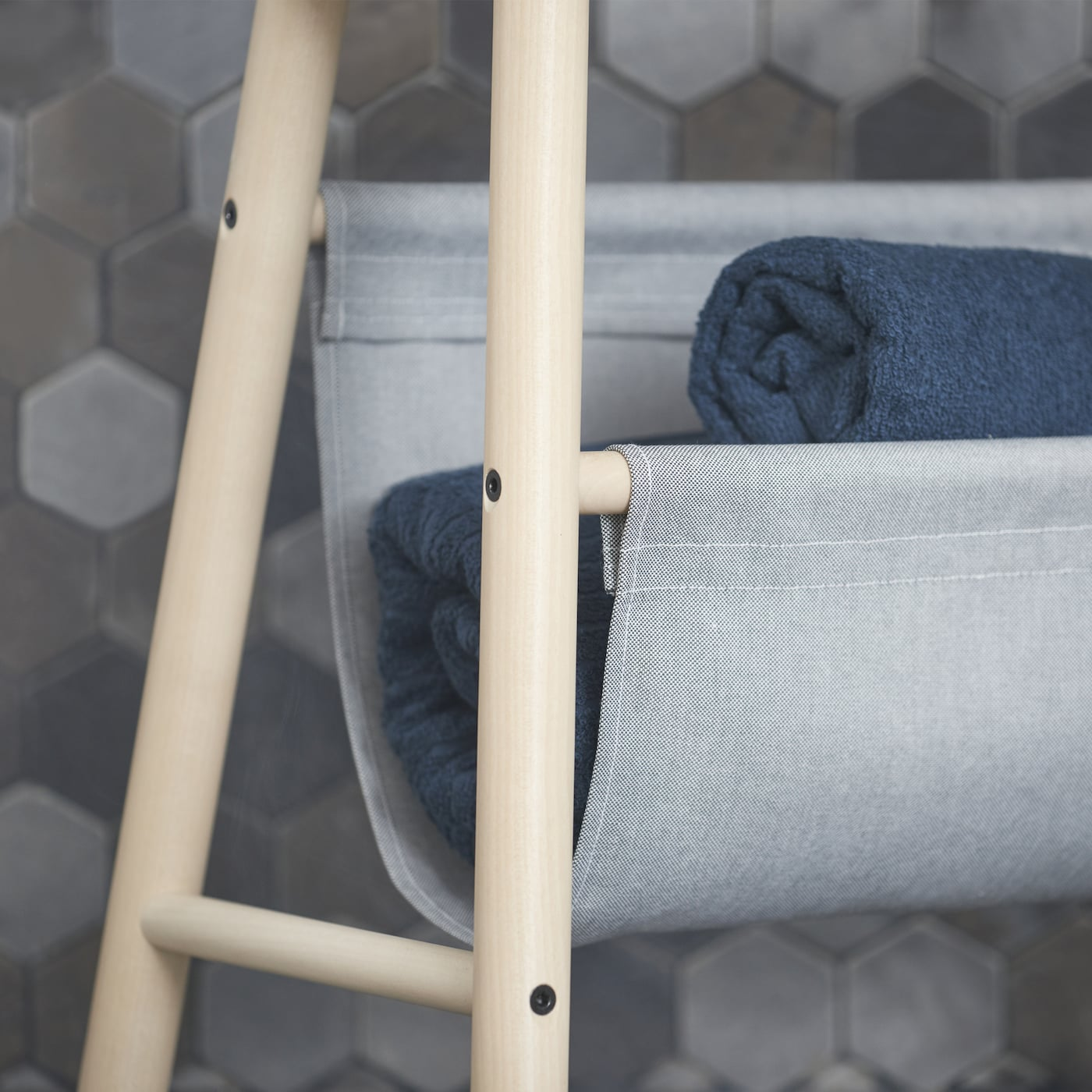 Close-up picture showing the textile pocket of IKEA VILTO storage stool that can store towels and toilet rolls. The light birch storage stool can also be used as a side table or magazine holder.