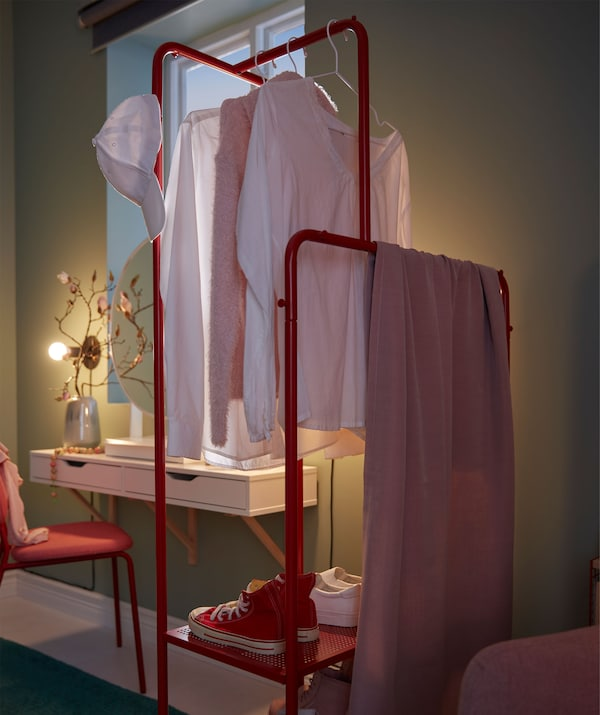 Clothes rack with garments and shoes placed perpendicular to the wall, as a room divider between recliner and make-up spot.