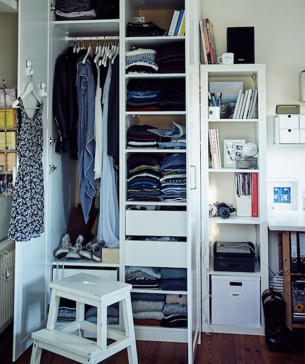 Clothes stacked on shelves and hanging from a rail inside Stine's wardrobe.