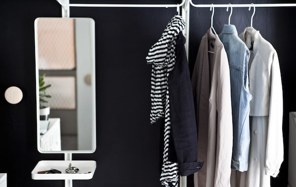 Coats, jackets and a mirror with a small tray hanging on a rail against a black wall.