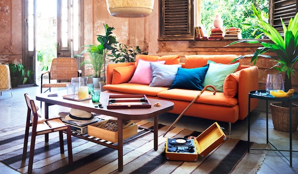 Coloured cushions placed on an orange SÖDERHAMN sofa in a living room. A coffee table holds drinks and a board game.