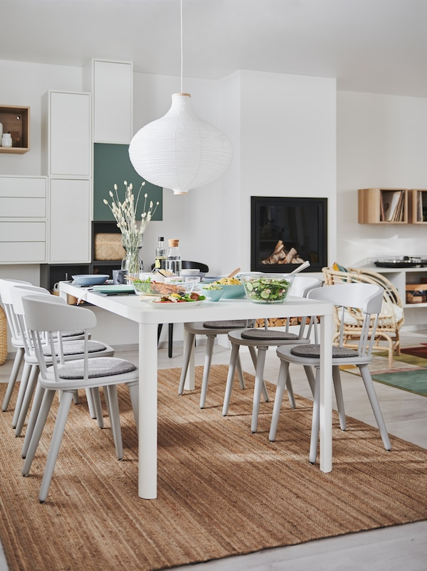 Combined living and dining room interior with fireplace, wall storage and a TINGBY dining table with OMTÄNKSAM chairs.