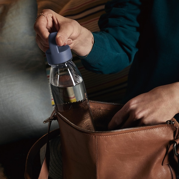 从一只棕色皮革袋中取出的可重复使用的 IKEA 365+ 塑料瓶。