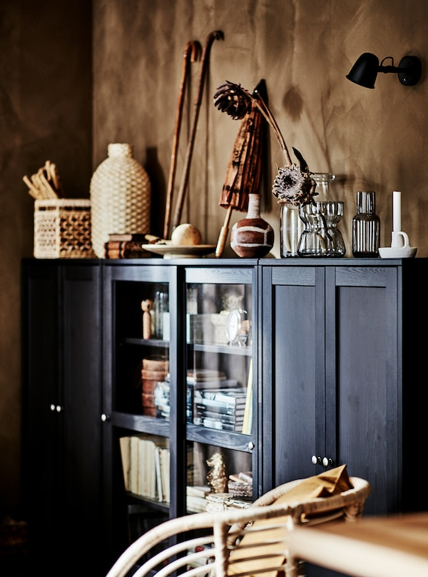 Corner of a living room with a dark, wide HAVSTA cabinet filled and covered with artful objects in natural materials.