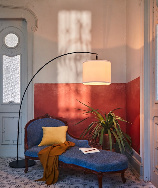 Corner of a room with refined materials and details. A SKAFTET floor lamp arch over a big plant and an elegant divan.