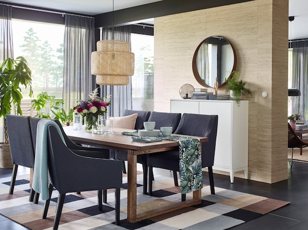 Create a nature-themed dining room and table setting with green hues from TORGET fabric and natural bamboo materials from SINNERLIG ceiling lamp.