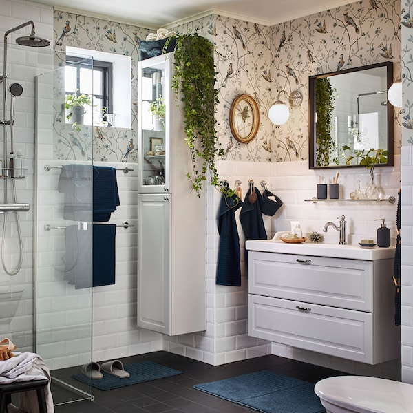 Create a relaxing atmosphere in your bathroom with IKEA GODMORGON white washbasin and white bathroom cabinet with glass doors. LILLHOLMEN nickel-plated wall lamps give a soothing warm glow for morning and night.