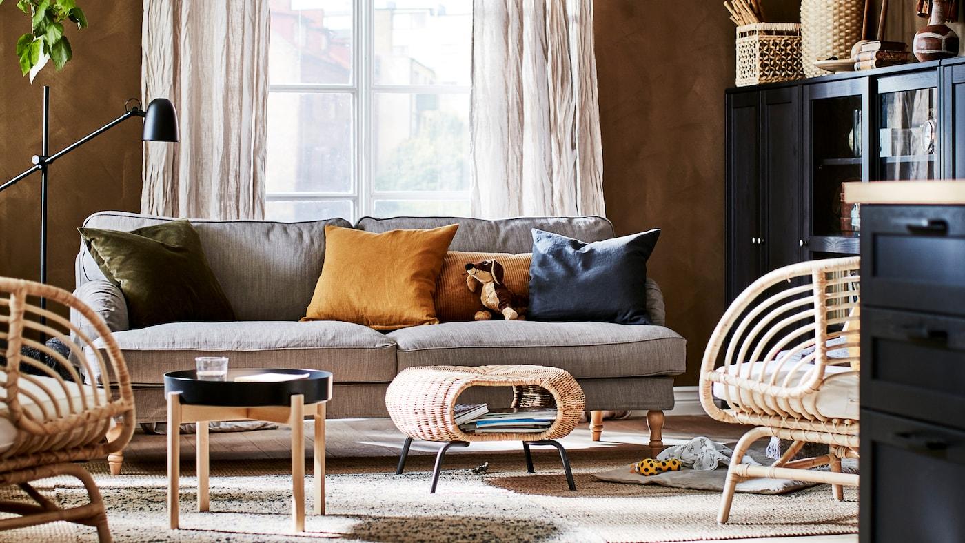 大地色系的客厅,配有装饰品、储物单元、座椅、边桌、脚凳和一盆植物。