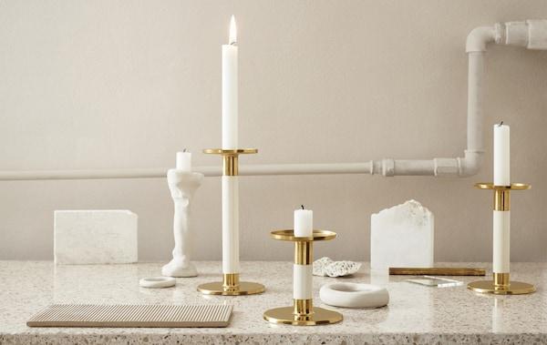 大理石台面上展示着象牙白和金色烛台。