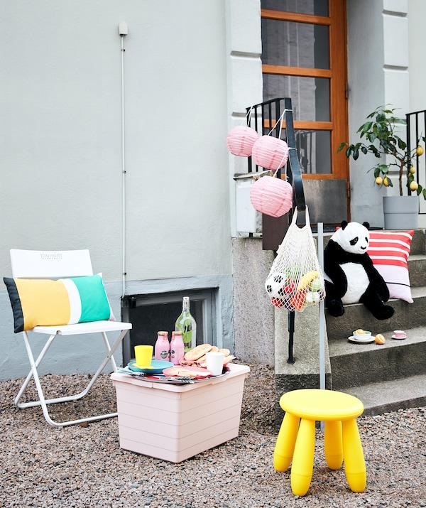 大楼外放着椅子、小桌子、食物和饮料、玩具和装饰物,适合野餐和游戏。