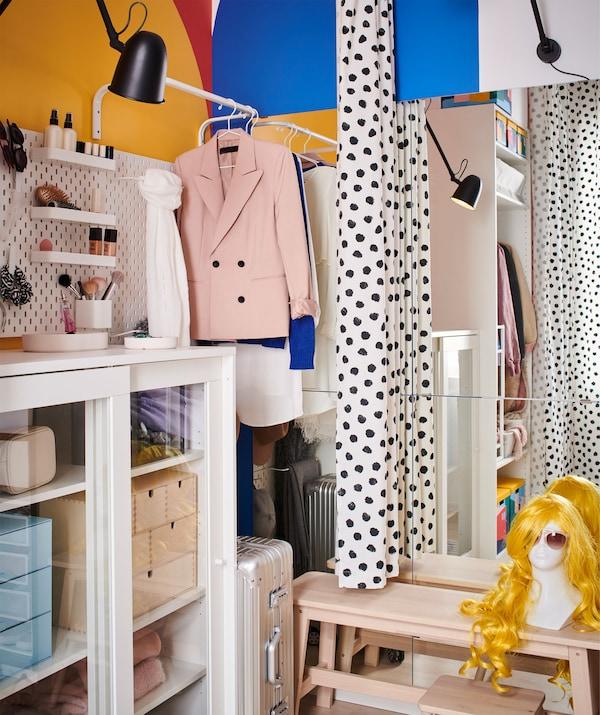 带储物空间的房间角落,挂帘的一边挂着衣服,另一边摆放着长凳、镜子和照明灯。