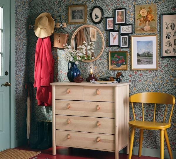 带挂钩的门厅,用于挂放衣服;一张黄色椅子和一个实心桦木制成的BJÖRKSNÄS 约纳斯 五斗抽屉柜。