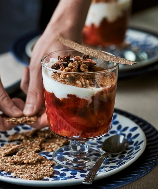 带花朵图案的蓝色盘子上放着甜食杯,里面盛有水果和酸奶。