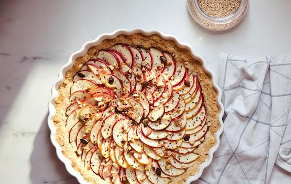 带灰色图案的白色厨房毛巾,旁边VARDAGEN 瓦达恩 烘饼盘中装着铺满薄苹果片的馅饼。