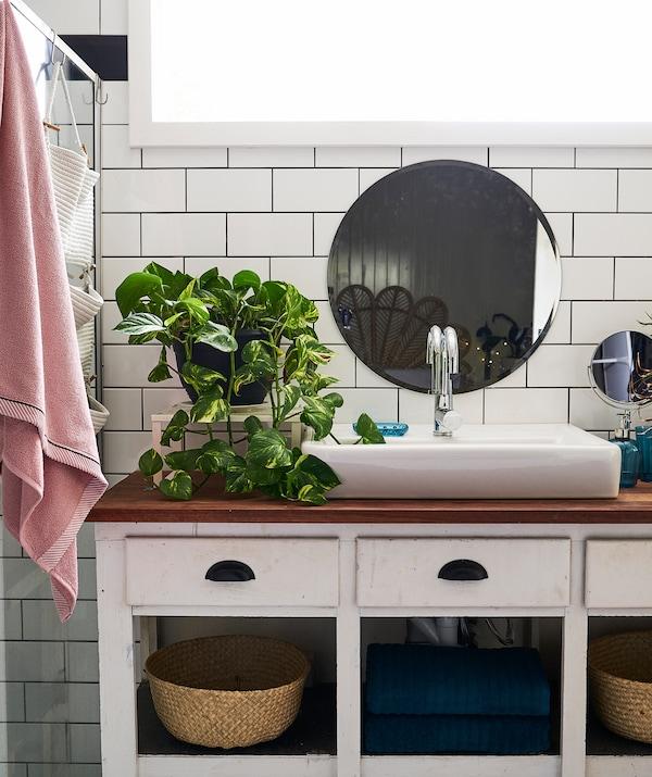 带木质台面的白色梳妆台上配有一个大型白色水槽并摆放着植物,上方的白色瓷砖墙上挂着一面圆形镜子。