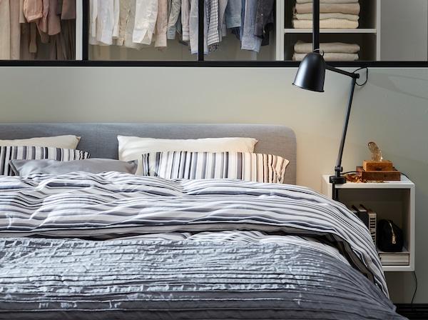 带软垫灰色床架,条纹床用纺织品,白色床边桌和黑色灯具。
