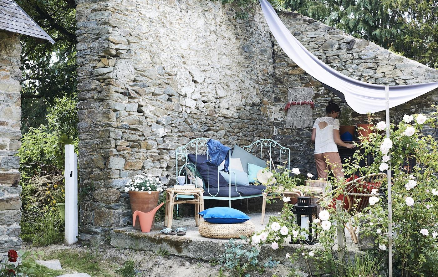 带围墙的花园里,摆放着凳子、椅子和配备有彩色靠垫的边桌。