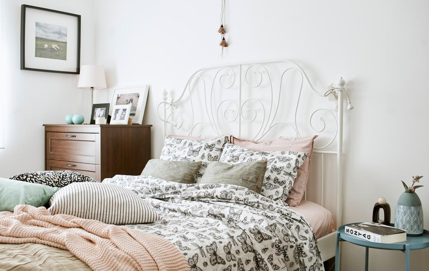 带有白色铸铁床头的床上,铺着饰有单色蝴蝶图案的被子,上面摆放着粉色的针织休闲毯和靠垫。