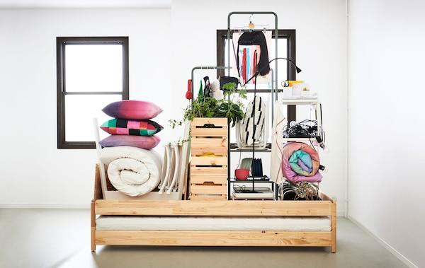 带有裸墙的房间或公寓室内设计。位于中央的床承载着小房子里的所有家具和必需品。