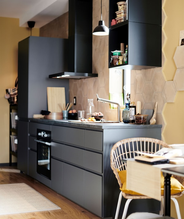 淡黄色房间里的深色单面墙厨房,墙上安装着抽油烟机。