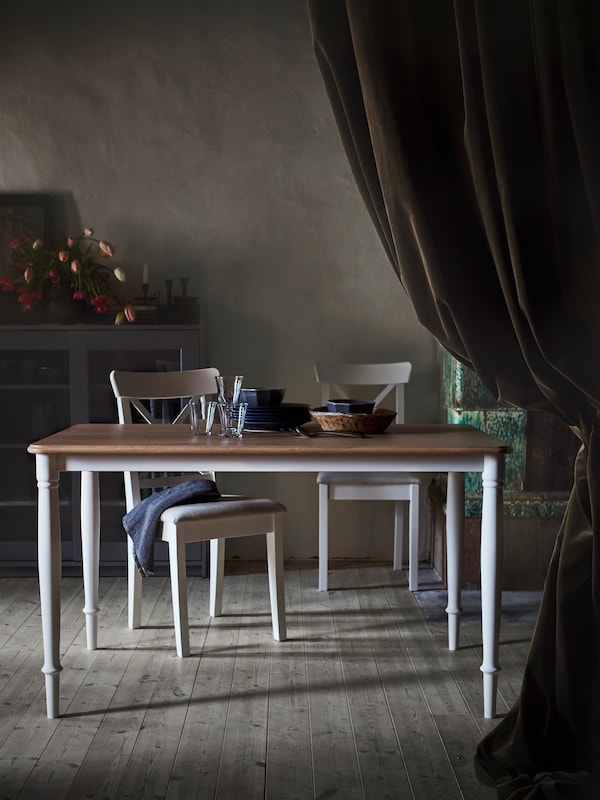 DANDERYD dining table with an oak veneer table top and white legs placed in a dark room with white chairs.