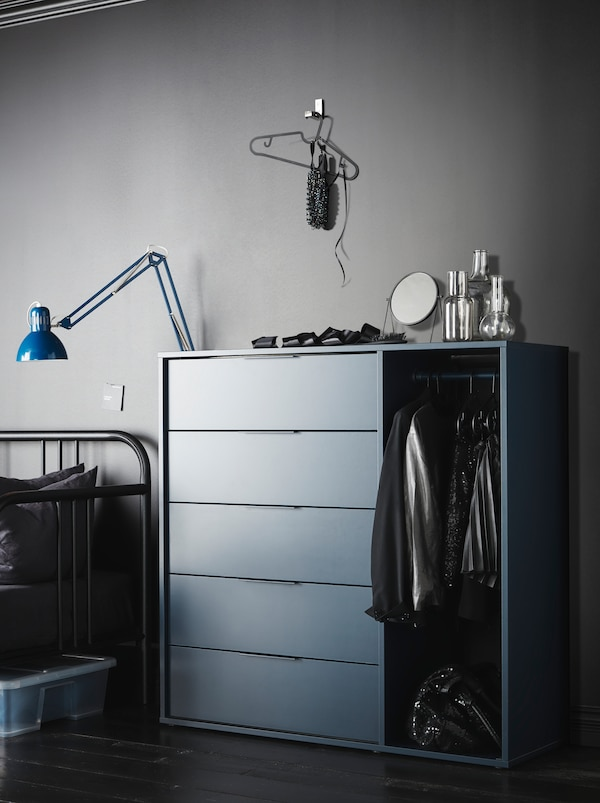 Dark NORDMELA chest of drawers – clothes hanging from its rail, mirror and decorations on top – in a minimalistic, grey room.