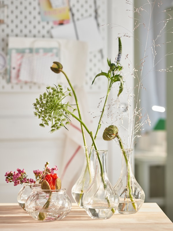 Different-height VILJESTARK glass vases holding a single flower or a few stalks, all placed on a wooden kitchen surface.
