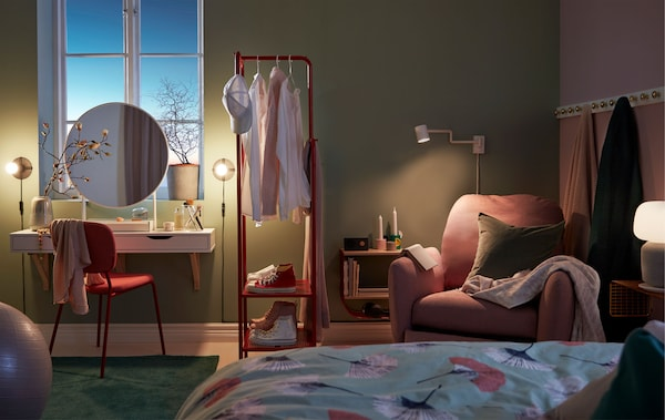 Dimly mood-lit bedroom with a make-up nook, room-dividing clothes rack and reading corner with recliner.
