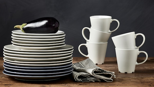 DINERA beige/white mugs are stacked on a worktop next to a stack of beige and grey/blue plates in various sizes.