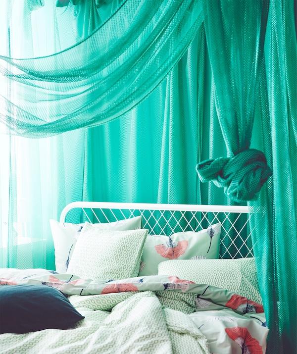 Draped green IKEA GRÅTISTEL net curtains letting through a little light.