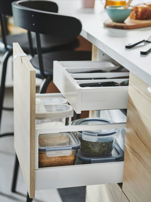 Drawn-out ASKERSUND front of a kitchen island, revealing a two-level drawer solution with both cutlery and food containers.