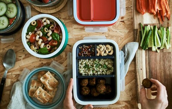 多个装好食物的午餐盒。其中一只午餐盒的格子里装了不同的食物,一个塑料食品盒内装了意面沙拉。