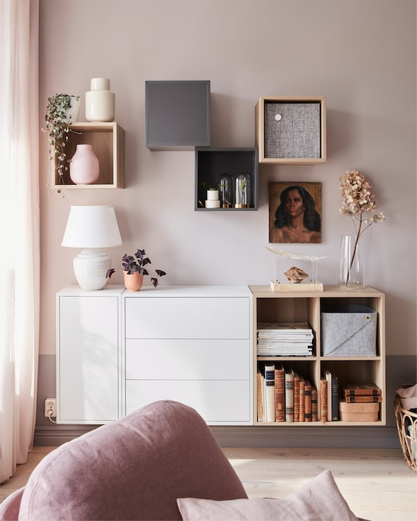 EKET cabinet in white-stained oak effect, with plants and a lamp placed on it, situated in a living room with a recliner.