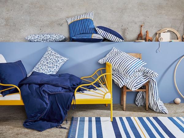 儿童床上展示着蓝色和白色 SÅNGLÄRKA 桑拉尔克 纺织品系列中的靠垫,以及一款饰有条纹和花朵图案的被套。