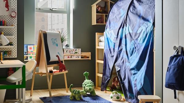 儿童房里放着一张带KURA 库拉 床帐的KURA 库拉 两面用床,还放着许多玩具恐龙。床旁放着MÅLA 莫拉 画架。