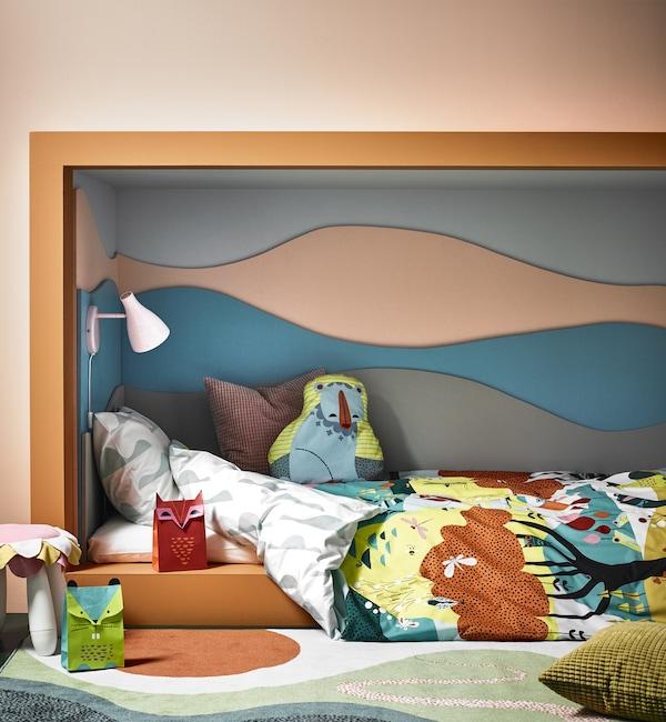 儿童房内放有一张壁室床,床上铺着饰有云朵、树木、动物和花朵图案的被套。