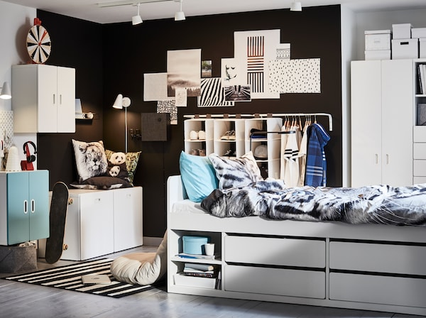 儿童房饰以白色、蓝色和黑色,搭配白色床架、老虎图案的被套和枕套以及蓝色细节。