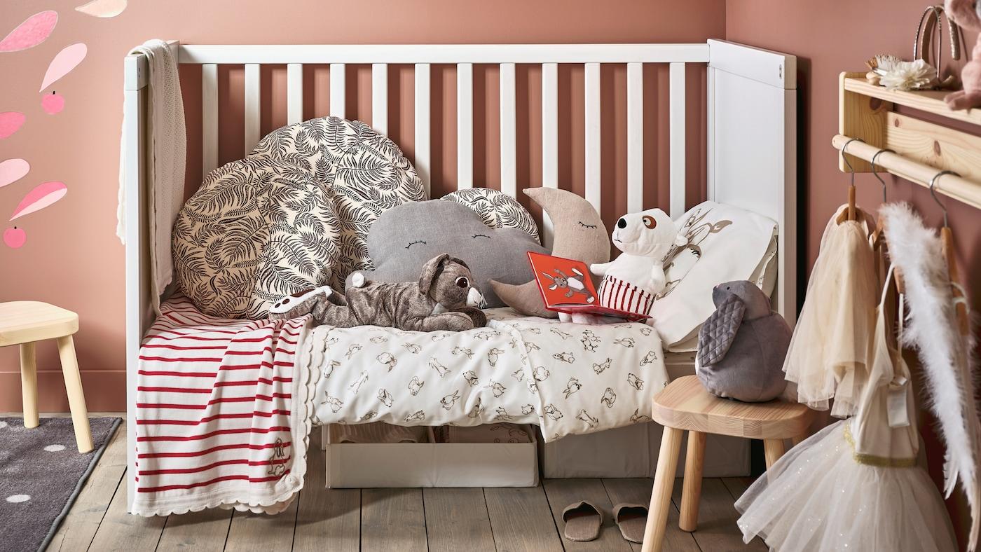 儿童房一角放着SUNDVIK 桑维 婴儿床,铺着RÖDHAKE 吕哈克 床上用品,上面放着舒适的靠垫和毛绒玩具。