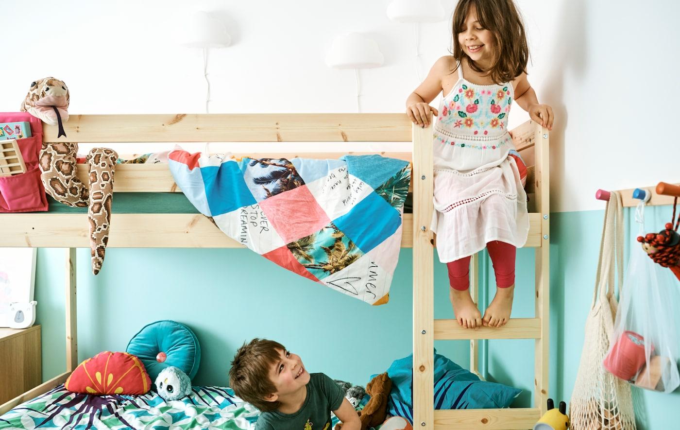 儿童房中,小男孩坐在双层床下铺,抬头看正拾级而上去往上铺的姐妹。