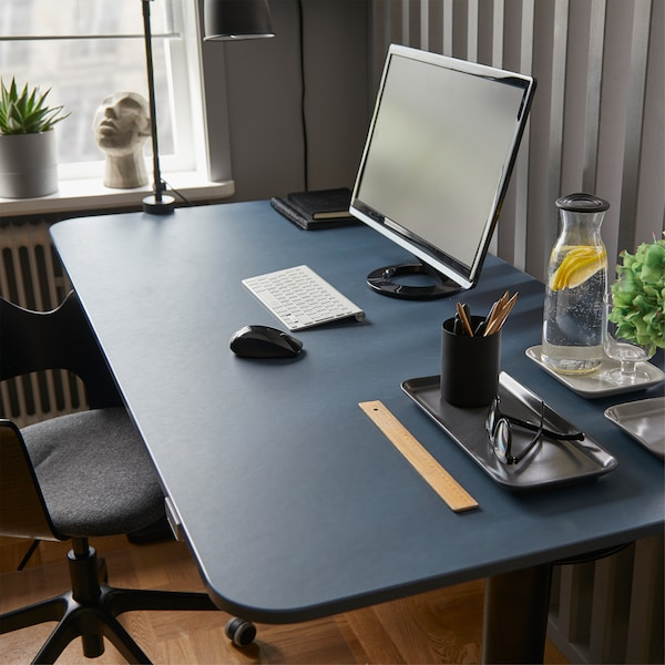Ergonomic BEKANT linoleum blue/black sit/stand desk with a computer screen, water bottle and glass and various office items.