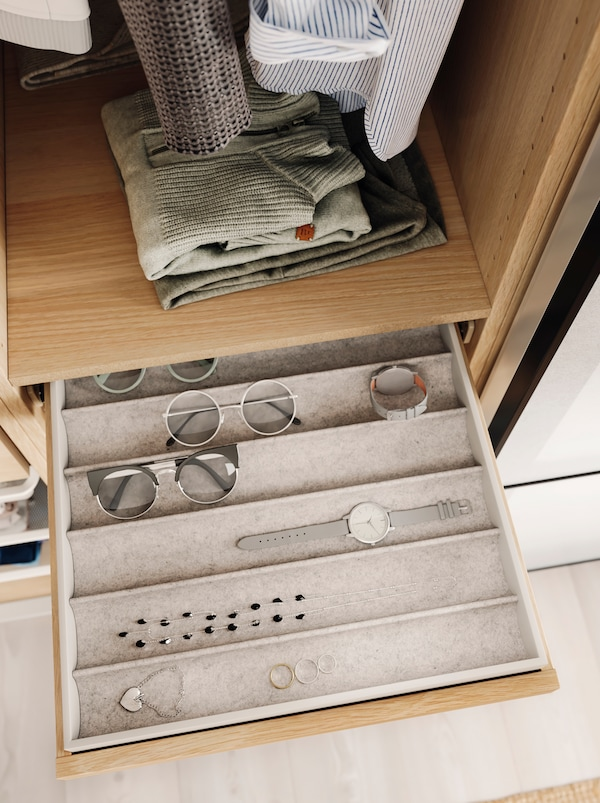 Eyewear, a watch and jewellery in neat rows in a KOMPLEMENT insert within a pulled-out, shallow drawer in an open wardrobe.