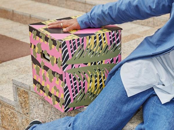 方形的 OMBYTE 欧姆比特 搬家盒饰有粉色和绿色的图案,灵感源自植物和野生动物。